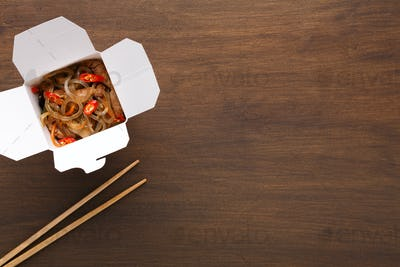 Asian food in delivery box on wooden table