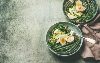 Healthy vegetarian breakfast bowls over grey concrete background, copy space