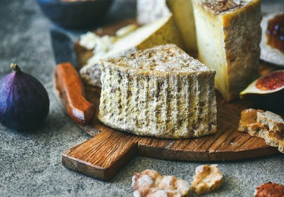 Cheese assortment, figs, honey, bread and nuts on board
