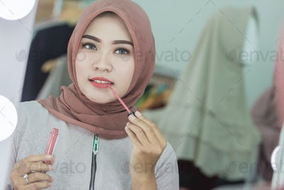 beautiful asian muslim woman with hijab applying lipstick