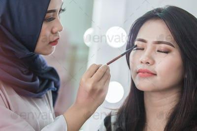 Make-up artist applying cosmetic