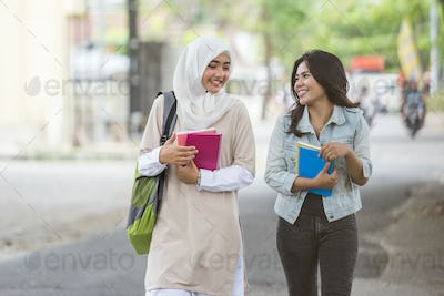 two asian student walking on campus
