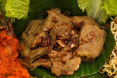 indonesian dish rendang on nasi tumpeng