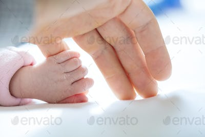 Newborn baby girl holding mother's little finger