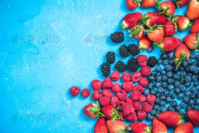 Market fresh mixed berry fruits, top view, border background