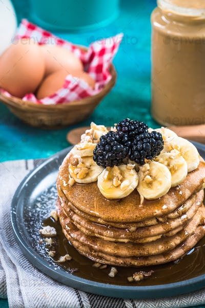 Pancakes with blackberries,walnuts,banana and maple syrup