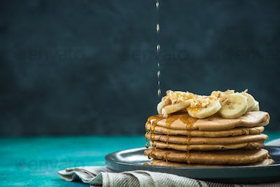 pouring maple syrup over pancakes pile