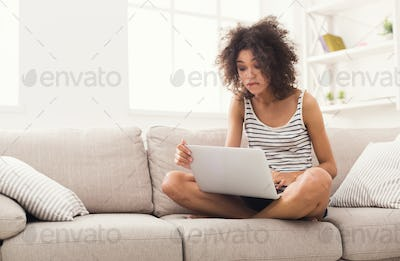 Young girl with laptop sitting on beige couch