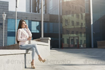 Confident young businesswoman talking on smartphone
