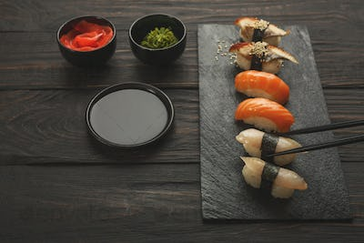 Set of sushi on black wood background, closeup