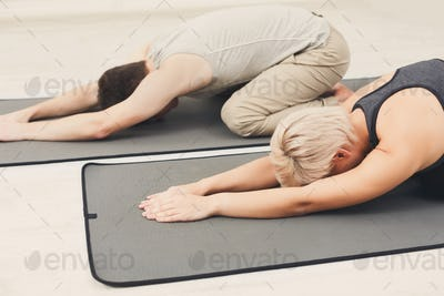 Couple training yoga in child's pose.