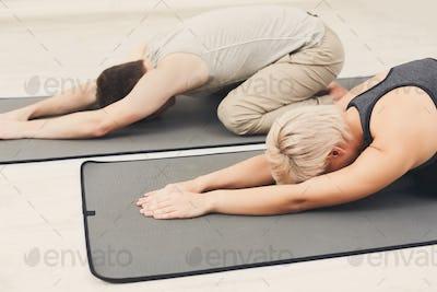 Couple training yoga in child's pose.