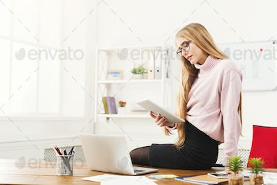 Business woman reading digital tablet at office