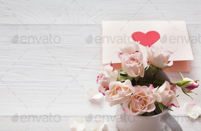 Pink rose flowers bouquet and handmade greeting card on white rustic wood