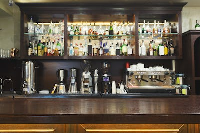 Bar counter with alcohol bottles assortment