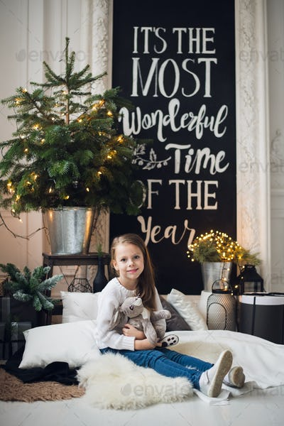 Christmas home decoration. A little girl girl sitting on a plaid on a floor. Very beautiful girl