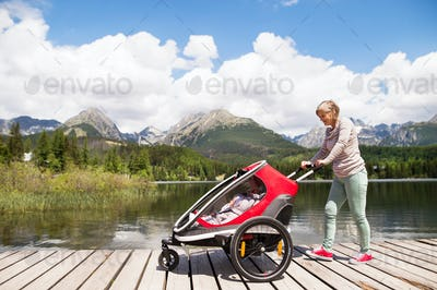 Senior woman and children in jogging stroller, summer day.