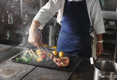 Chef cooking juicy beef steak at restaurant kitchen