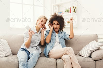 Two women listening music and sharing earphones