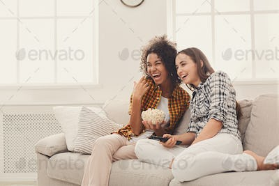 Smiling young women watching TV at home