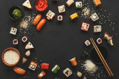 Sushi and rolls background, frame on black, top view.