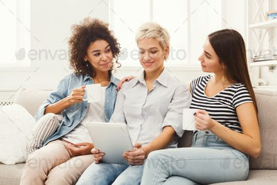 Three happy female friends using tablet and drinking coffee