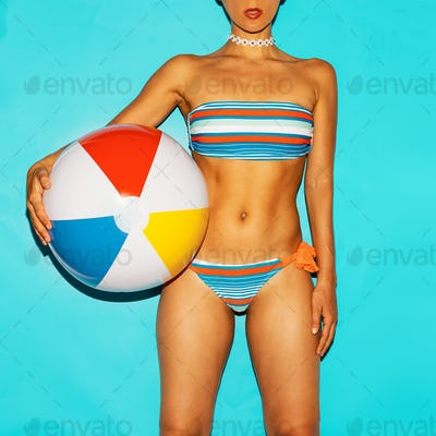 Girl in fashionable swimsuit and beach ball. Summer trend