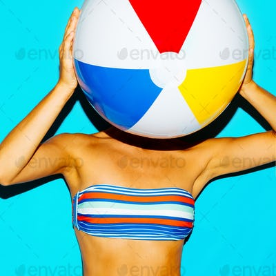 Tanned girl in a stylish bikini and with a beach ball. Beach sty