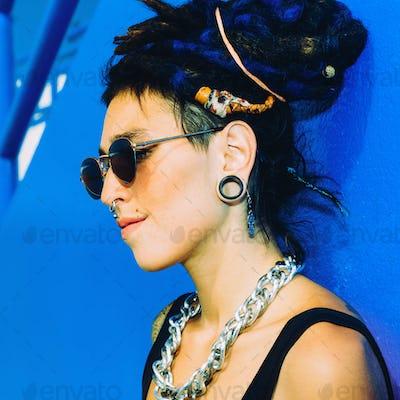 Fashion Spanish Girl with dreadlocks, piercings, tattoos and sty