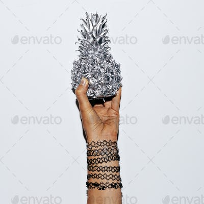 Hand in bracelets and silver pineapple. Minimal fashion accessor
