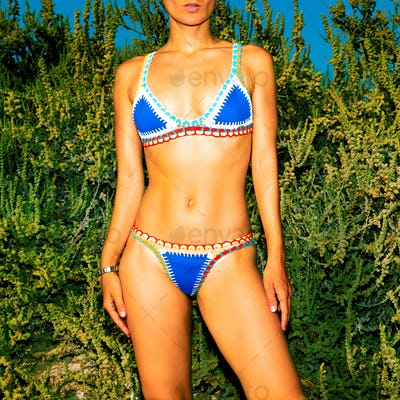 Girl. Beach style. Tanned body. Bikini fashion