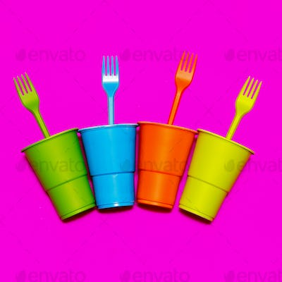 Plastic tableware. Minimal. Multicolored glasses and forks