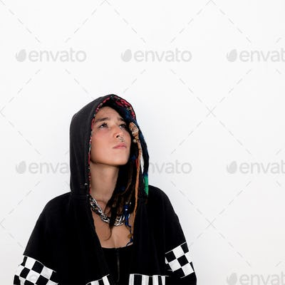 Latin teen with dreadlocks and piercings. In a black hoodie. Str