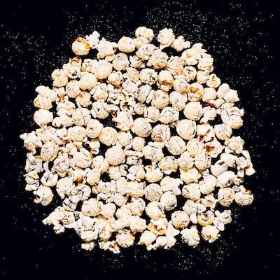 Popcorn on a black glitter background Minimal fashion
