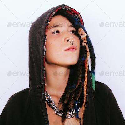 Latin girl with dreadlocks and piercings. In a black hoodie. Str