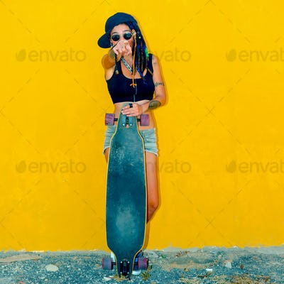 Cool Frick Teenager girl on a yellow wall background with a skat