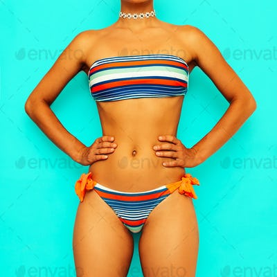 Girl in a striped swimsuit. Beach style fashion