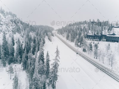 Aerial view of snow-covered road adn wood in the countryside Finland