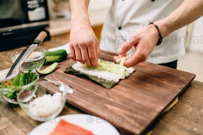 Male cook hands making sushi rolls, seafood