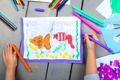 Top view of child hands with pencil painting picture