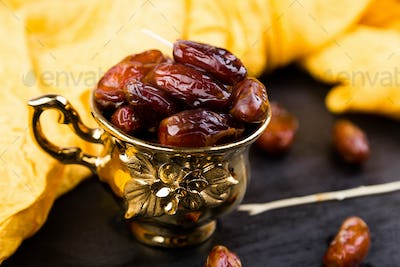 Dry fruit dates in golden cup near slate black heart.
