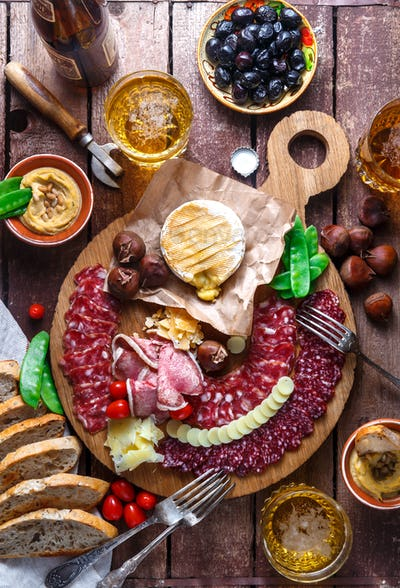 Mix of different snacks and appetizers: sausage, bread, olives, cheese, chestnuts.Top view.