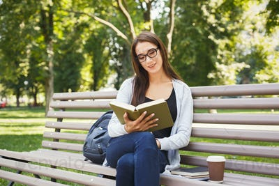 Young woman reading book in park copy space