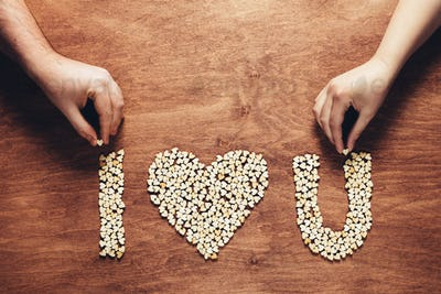 """Two hands composing """"i love you"""" writing."""
