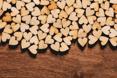 Little hearts on wooden background.