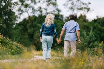 Old couple holding hands on a walk.