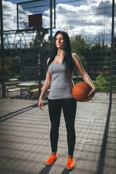 Female basketball player training outdoors on a local court