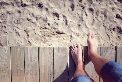 Man barefoot stepping off boardwalk onto the beach sand