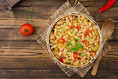 Vegetarian porridge from Turkish couscous with vegetables. Dietary menu. Vegan cuisine. Top view