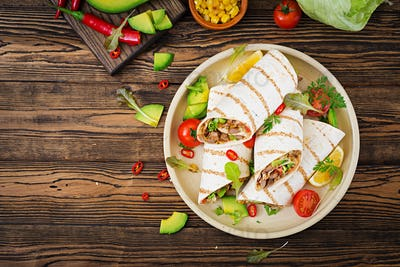 Burritos wraps with beef and vegetables on a wooden background.